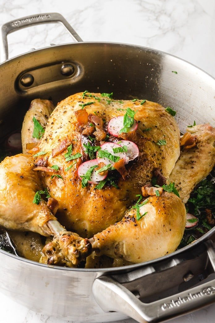 roasted chicken in a dutch oven with radishes and kale