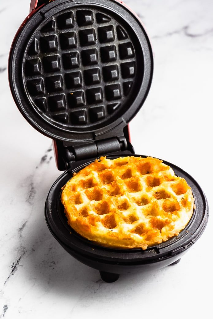 mini cheddar waffle cooking in a waffle maker