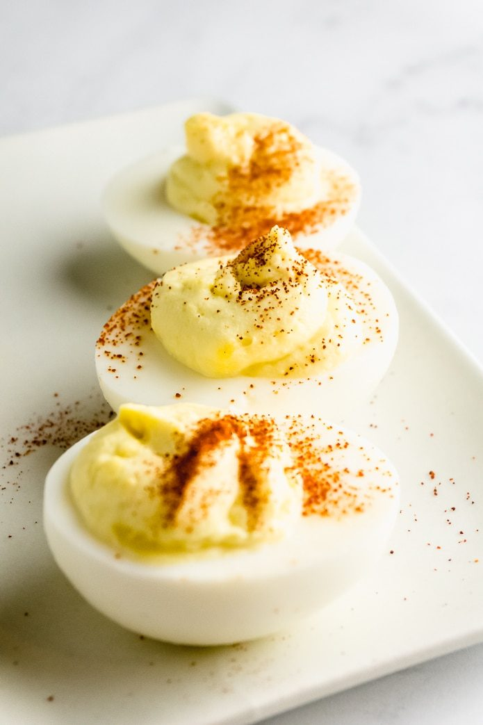 three keto deviled eggs with paprika