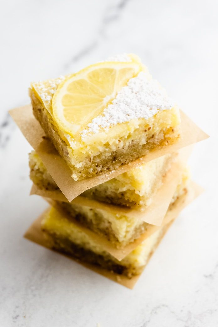 stack of keto lemon bars with powdered sweetener